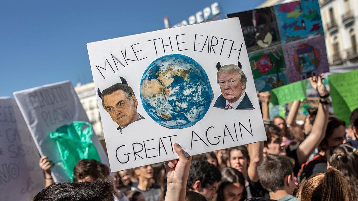 2019 г. Протесты в Испании против экологической политики крупных стран. На фото студент держит плакат с изображением президента США Дональда Трампа и президента Бразилии Жаира Болсонару