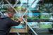Владелец магазина в Нью-Йорке заклеивает витрину скотчем.