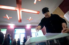 Женщина опускает бюллетень в урну для голосования на одном из избирательных участков Тбилиси.