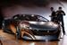 Peugeot ONYX                                           На «домашнем» автосалоне в Париже Peugeot вновь старается удивить мир своим концептом, на этот раз гибридным суперкаром Onyx. Дизайн машины построен на контрасте материалов и цветов. Передние крылья и двери сделаны из отполированных листов чистой меди и, оставаясь безо всякого покрытия, предназначены процессу благородного естественного старения. Остальные кузовные панели изготовлены из углеволокна и окрашены матовой краской. В интерьере используется войлок и материал из прессованной газетной бумаги, которому создатели придумали название Newspaper Wood. Купе приводится в движение гибридным агрегатом суммарной мощностью 600 л.с. Основной мотор — дизельный 3,7 л V8 — расположен по центру машины и приводит задние колеса через 6-ступенчатую секвентальную КПП. К прогрессивному суперкару прилагаются концептуальный велосипед и трехколесный гибридный скутер, выполненные в аналогичной стилистике и из тех же материалов.