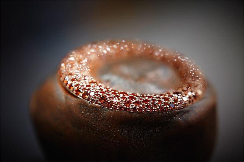 Циферблат Grappoli и возвышающийся над ним широкий, слегка асимметричный безель полностью покрыты россыпью из 980 драгоценных камней круглой огранки