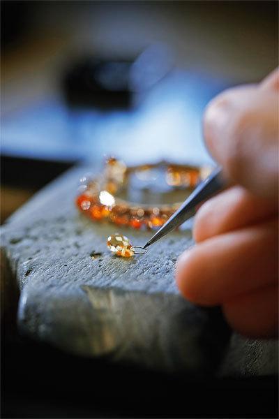 Близкие по размеру и цвету бриолеты закрепляются накольце из золота, которое затем надевается на корпус часов