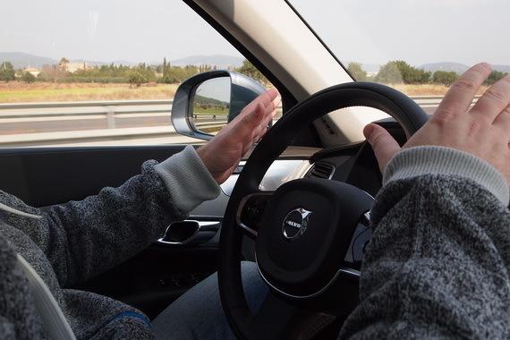 Водитель нового Volvo XC90 держит руки на весу над рулем: дорога поворачивает, руль тоже поворачивает, машина остается в полосе