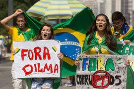 Демонстранты в Сан-Паулу несут плакаты «Дилма — вон», «Коррупция [в этом слове также перечеркнуты буквы PT – аббревиатура Партии трудящихся] — вон»