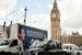 Грузовик с рекламным плакатом с портретами главных претендентов на пост премьер-министра — Дэвида Кэмерона и Эда Милибэнда, на Парламентской площади в Лондоне