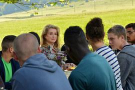 Судья (Катрин Денев) приехала в колонию-интернат отобедать с подростками, которых туда отправила (герой – напротив, вполоборота)