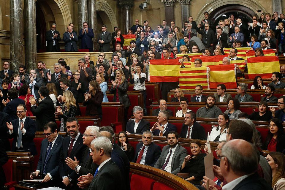 Депутаты парламента Каталонии держат флаги Испании и своей провинции