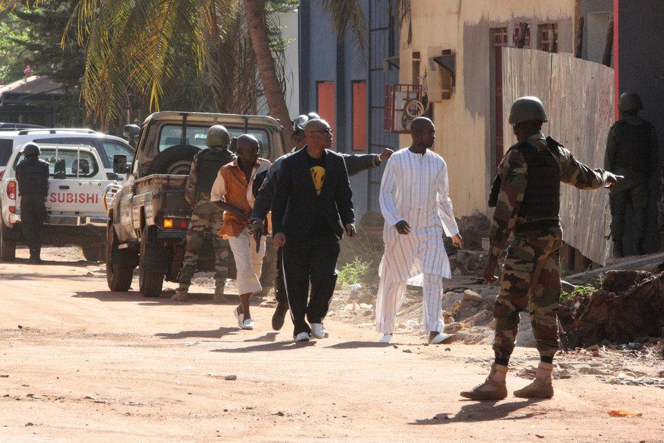 Военные сопровождают людей, спасшихся из отеля