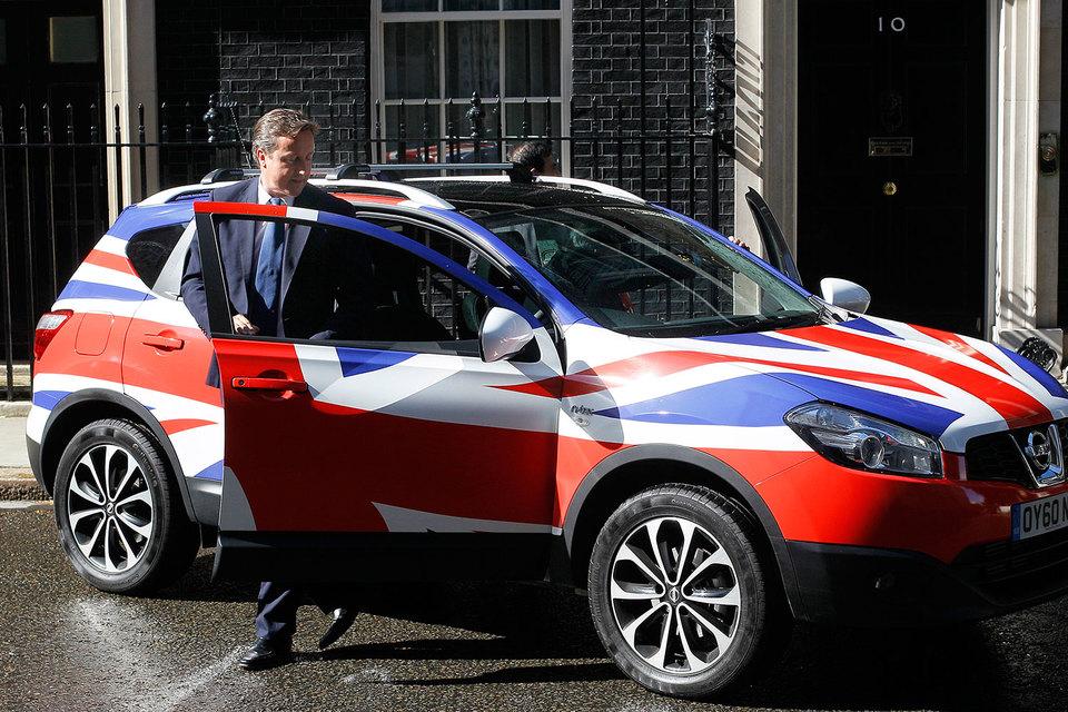 Премьер-министр Великобритании Дэвид Кэмерон в июне 2011 г. осматривает в Лондоне на Даунинг-стрит Nissan Qashqai, в запуск производства которого в стране японская компания инвестировала дополнительно 192 млн фунтов стерлингов