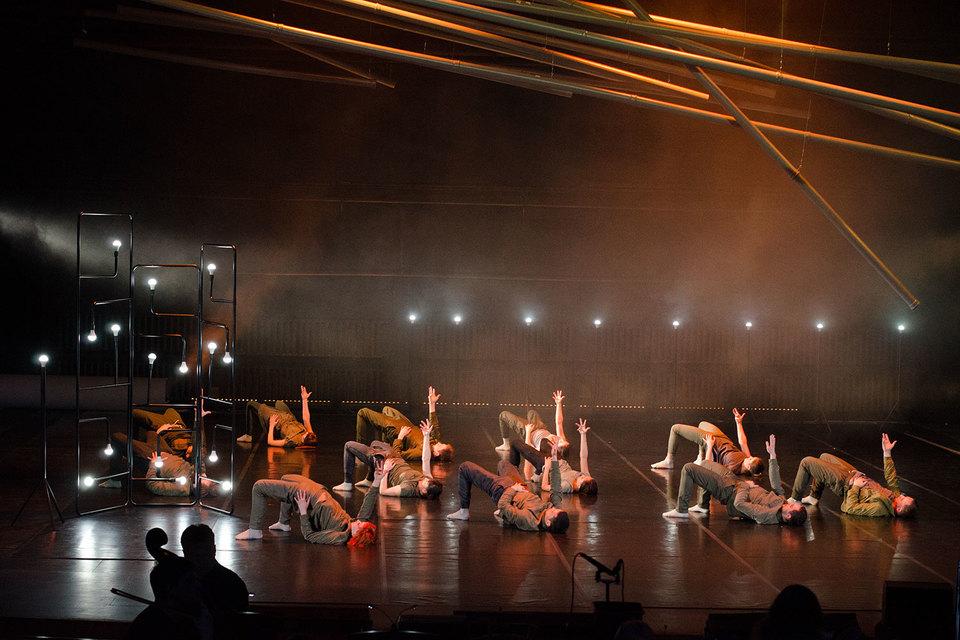 Ансамбль танцовщиков изображает ладную работу заводского механизма
