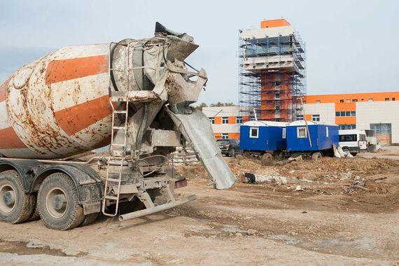 Специально на территории строительства были возведены четыре передвижных завода: три по изготовлению бетона и один - для асфальта (на заднем плане строящаяся аварийно-спасательная станция)