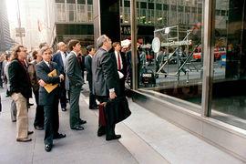 Люди на Манхэттене 19 октября 1987 г. смотрят через окно на экран с падающими котировками акций