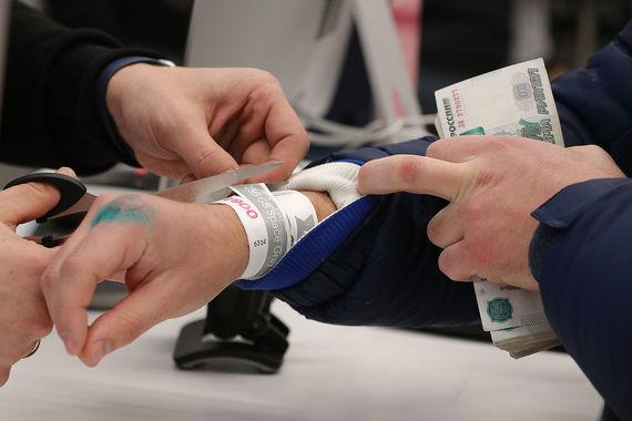 На фото работник магазина срезает браслет с номером с руки покупателя