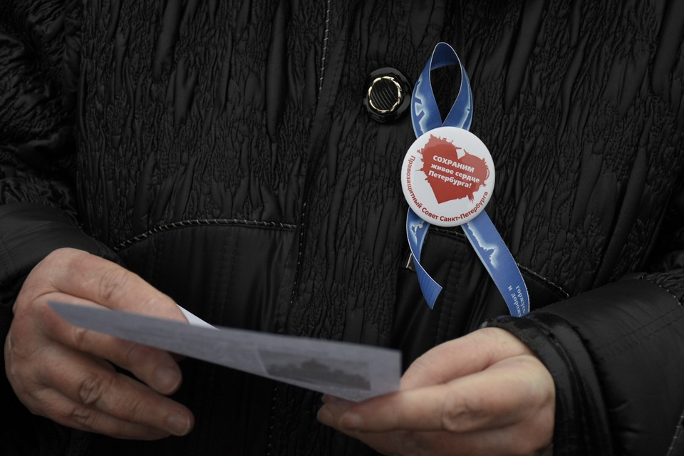 Вместе с синими ленточками у многих собравшихся были значки с надписью «Сохраним живое сердце Петербурга»