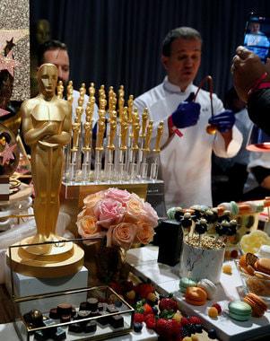 Перед церемонией в Голливуде проходят многочисленные приемы и вечеринки. Их непременная часть — символика премии: «Оскарами» украшают столы и помещения, а шеф-повара готовят съедобные статуэтки, в основном пирожные или закуски. На фото: актриса Элизабет Тейлор на церемонии 1960 г. и подготовка к церемонии 2018 г.