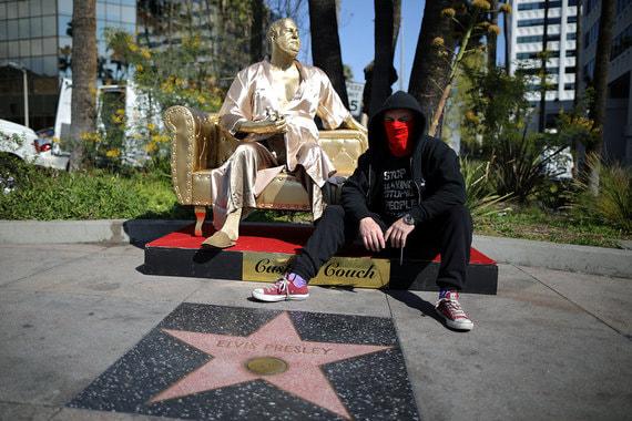 """2 марта 2018 г. Уличные художники Plastic Jesus (на фото) и Джошуа Монро установили в Голливуде, недалеко от киноцентра, где вручают премию """"Оскар"""", позолоченную статую продюсера Харви Вайнштейна. Название арт-объекта – """"Диван для кастинга"""""""