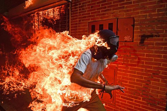 Организаторы международного конкурса World Press Photo объявили победителей. Главный приз достался фотографу из Венесуэлы Роналдо Шемидту за снимок эпизода митинга против президента страны Николаса Мадуро. В объектив фотографа попал 28-летний Виктор Салазар, он загорелся, когда рядом взорвался бензобак мотоцикла. Салазар выжил, получив ожоги первой и второй степени. Эта же фотография стала лучшей в номинации «Главная новость»