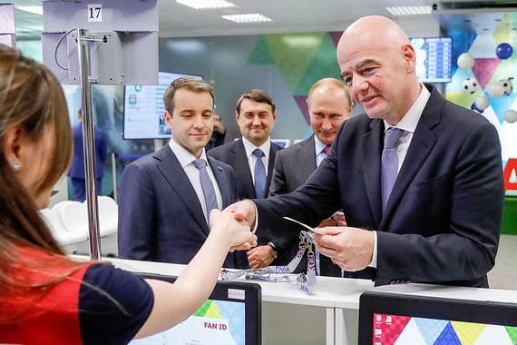 Министр связи Николай Никифоров (слева) с помощью автомата электронной очереди распечатал Владимиру Путину и президенту FIFA Джанни Инфантино (справа) талоны, с которыми они подошли к стойкам регистрации. Там операторы выдали им ID-карты