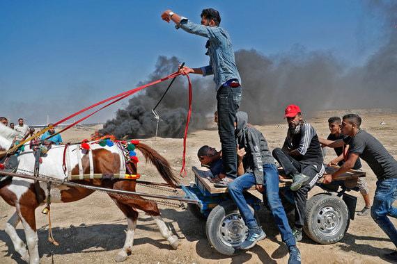 Палестинцы вывозят раненого демонстранта после столкновений с полицией у границы Израиля