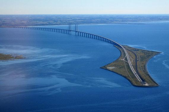 Самая длинная совмещённая дорога и железнодорожный мост в Европе Эресуннский мост (мост-тоннель) Страна: Швеция, Дания Длина: 7,8 км Открытие: июль 2000 Стоимость: $3,8 млрд Совмещённый мост-тоннель, включающий двухпутную железную дорогу и четырехполосную автомагистраль через пролив Эресунн. Это самая длинная совмещённая дорога и железнодорожный мост в Европе, соединяющие столицу Дании Копенгаген и шведский город Мальмё. Мост соединяется с тоннелем «Дрогден» на насыпном острове Пеберхольм. 4-километровый тоннель представляет собой соединение 5 труб: две – для поездов, две – для автомобилей и одня – для аварийных ситуаций.