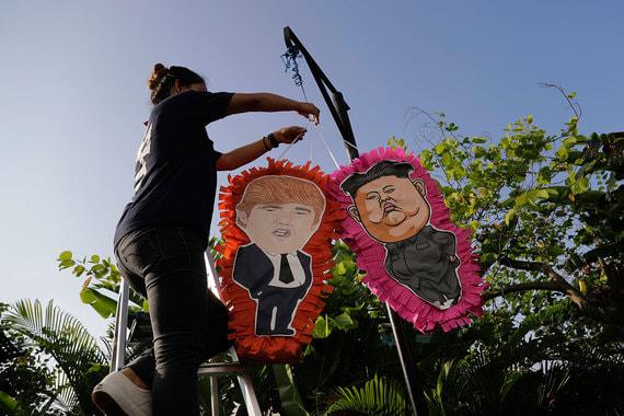 Сотрудник местного ресторана вывешивает пиньяты (полая игрушка из папье-маше) с шутливыми изображениями Трампа и Ким Чен Ына перед входом в заведение