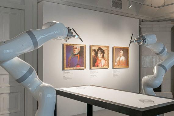 Роботы рисуют узоры на основе данных южнокорейского фондового рынка. На заднем плане – «Портреты семьи де Белами», пока что самые успешные произведения, созданные искусственным интеллектом